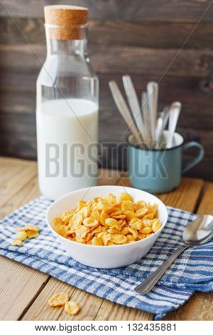 Tasty corn flakes in white bowl with bottle of milk. Rustic wooden background with plaid blue napkin. Healthy crispy breakfast snack.