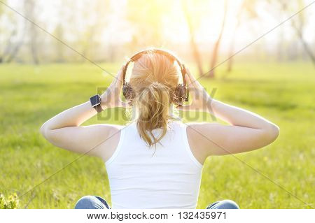Young woman sitting on grass in Park listening to music on headphones