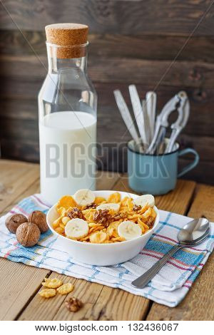 Tasty corn flakes with walnuts and banana in bowl with bottle of milk. Rustic wooden background with plaid napkin. Healthy crispy breakfast snack.