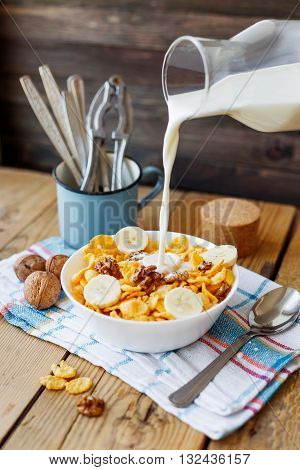 Milk from a bottle flows into the bowl with tasty corn flakes with walnuts and banana. Rustic wooden background with plaid napkin. Healthy crispy breakfast snack.