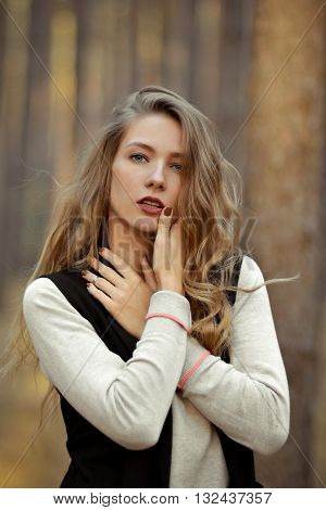 Glamorous, fashionable, sexy, sexual, seductive girl opens her mouth. Beautiful, attractive girl, model with sexual, seductive look, eyesight, red lips, long curly light hair outdoor, in summer, autumn forest, hand