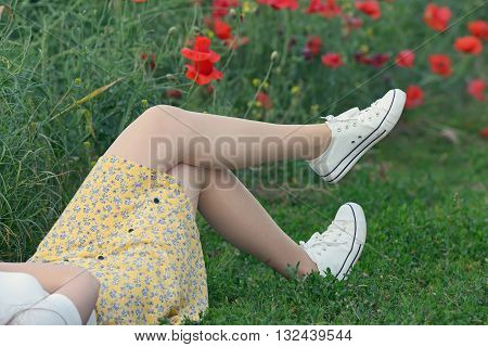 young girl lying on poppy field, close up