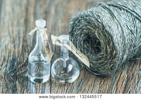 glass bottles on a wooden surface with skein of jute twine