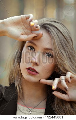 Closeup portrait of very beautiful, attractive stunning, perfect girl. Fashionable girl with opened mouth, hands near the cute, nice face, light, white, pure skin, red lips, shiny, light, long, perfect hair, trend.