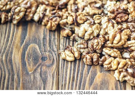 Walnut kernels on rustic old wooden table. Chopped walnuts.