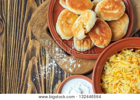 Traditional homemade pies with cabbage and sauerkraut on the plate on wooden board. Savory stuffed patties also known as pastel, pate or piroshki. Fried russian pastry pirozhki on wooden background.