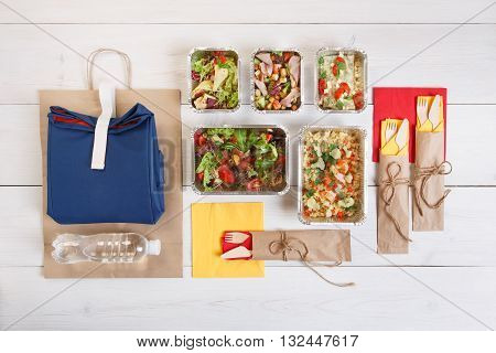 Healthy food delivery, take away of fitness nutrition, salads and meat in aluminium boxes, flat lay and top view.