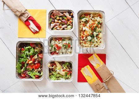 Healthy food delivery, take away of fitness nutrition, salads and meat in aluminium boxes, flat lay and top view at white wood