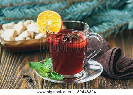 Hot red mulled wine on wooden background decorated blue spruce branches, with christmas spices, orange slice, fresh mint, cloves, anise and cinnamon sticks, close up.