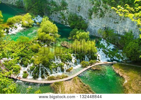 Beautiful landscape, waterfall, clear green water and wooden pathway in the Plitvice Lakes National Park in Croatia. Beautiful world. Panoramic view.