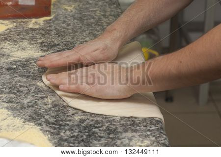 Man chef with raw pizza. Young male in uniform preparing pizza on table.