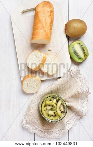 Canned kiwi in jar and bread slices top view. Focus on sliced kiwi in jar
