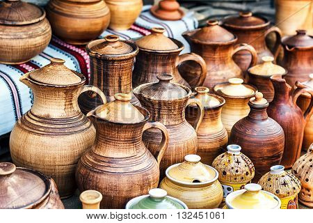 Group of traditional handmade pottery for sale at the market. Ukrainian handmade earthenware utensil. Souvenirs From Ukraine in ethnic style.
