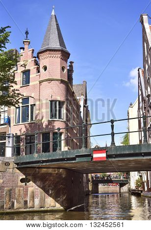 Canal of Amsterdam with bridges and decorative cobblestone house with turret.