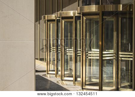 Architectural Revolving doors at a front entrance to a downtown building used for entering and exiting.