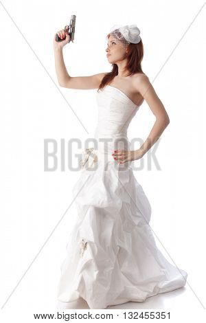 Young woman in a wedding dress with gun on a white background.