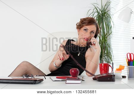 Businesswoman speaks by phone at office.