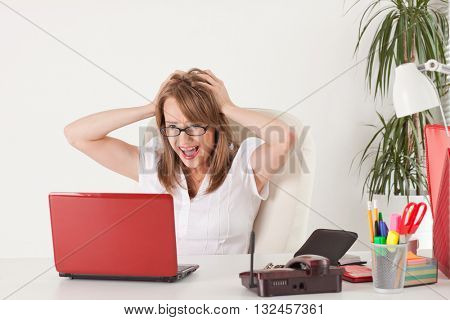 Stressed  business woman with  laptop in the office.