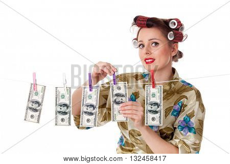Young housewife is hanging hundred dollar bills on clothesline on a white background.  Money concept.