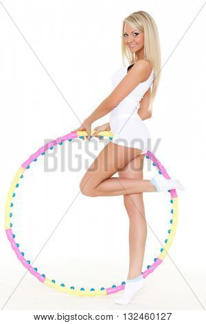 Young sporty woman with a hula-hoop on a white background.  Fitness.