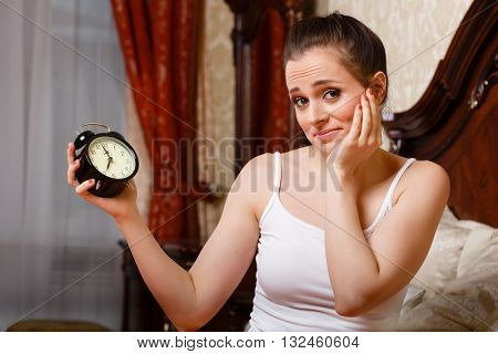 Unhappy young woman  looks at an alarm clock, sitting in a house bed. Has overslept.
