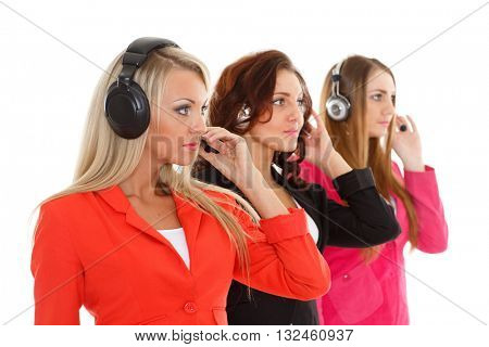 Happy young business women with headset on a white background. Operators of support service. Selective focus on first businesswoman.