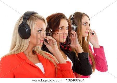 Happy young business women with headset on a white background. Operators of support service. Selective focus on second businesswoman.