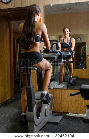 Beautiful sports woman exercising on the bicycle in the gym.