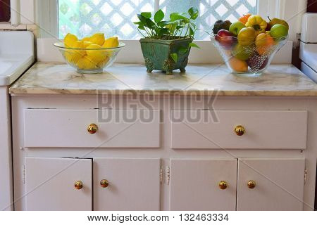 Older kitchen drawers and cabinets with assorted fruit baskets on the counter