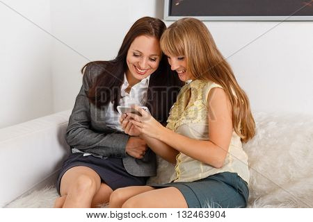 Two young business women with mobile phone sit on sofa in the office.