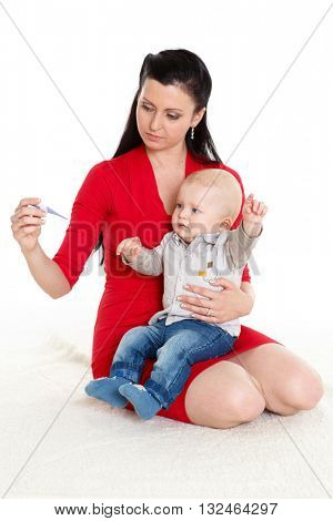 Young mother with  thermometer and sick baby sit on a white background.