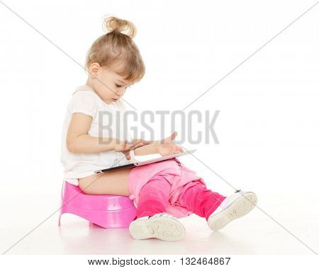 Pretty little girl with computer tablet  sits on a pink baby potty on a white background.