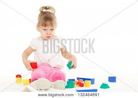 Little resentful girl plays with children blocks set on a white background. Learning toys and early development.