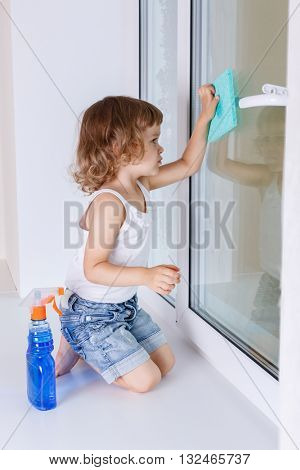 Serious little girl cleaning windows in the house. Mother's assistant.