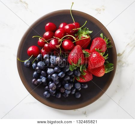 Summer Berries In Bowl On Marble Table, From Above