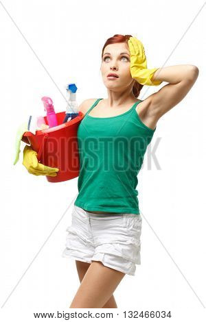 Young redhead woman is holding bucket with cleaning supplies on a white background. Housekeeping. Cleaning woman.