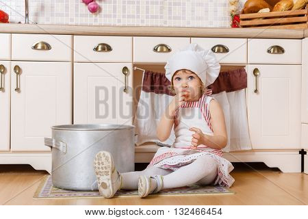 Little girl in apron and cap of the cook sitting  in the kitchen in the house. Mother's helper. 2 year old.