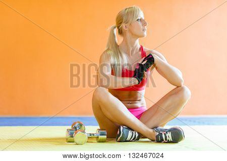 Beautiful young sports woman with dumbbells sits on a floor in the gym