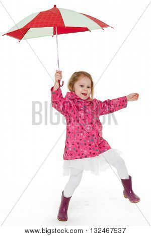 Cute cheerful little girl in raincoat and rubber boots with umbrella stands on a white background.  3 year old.