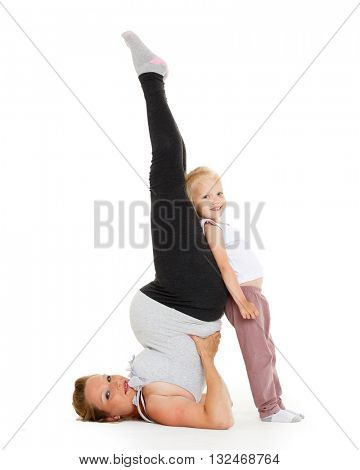 Young pr�©gnant woman with small daughter are doing sports exercises on a white background. Healthy family.