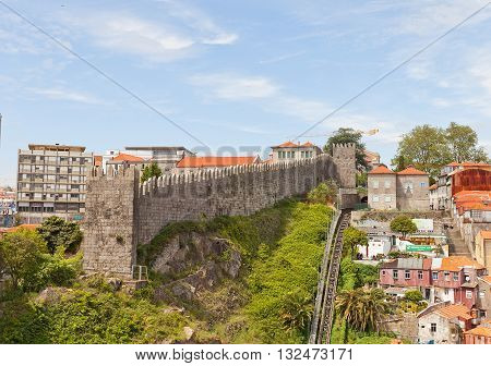 PORTO PORTUGAL - MAY 25 2016: City defensive rampart in Porto Portugal (UNESCO site). Completed in 1370 in the reign of King Ferdinand I so usually called as Ferdinand Walls (Muralha Fernandina)