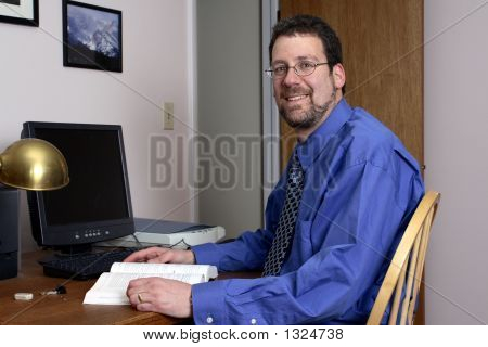 Middle-Aged Man Working And Smiling