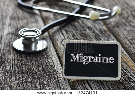 Medical Concept-Migraine word written on blackboard with Stethoscope on wood background