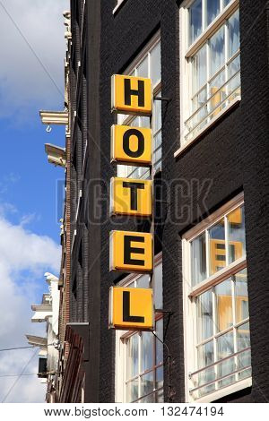 Vertical yellow Hotel sign over the entrance to the brick building in Amsterdam
