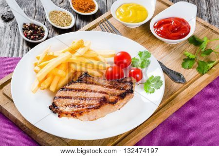 grilled pork chops on a white dish with french fries cherry tomatoes cilantro leaves and spices on a wooden table close-up