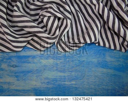 striped fabric stowed in a fold on the blue wooden boards