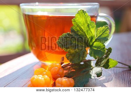 Cup of tea and a sprig of cloudberry berries and leaves