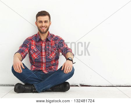 Portrait Of Happy Handsome Young Man Against White Wall.