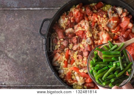 Adding French bean on the pan with cooking paella top view
