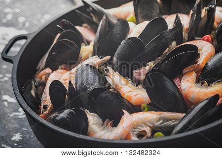 Paella in the pan on the metal background horizontal